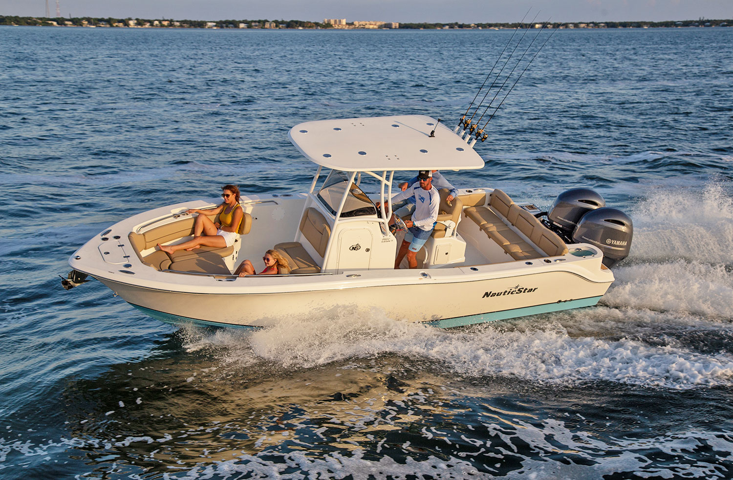 Man captaining the NauticStar 2602 Legacy with a woman, girl, and boy on board
