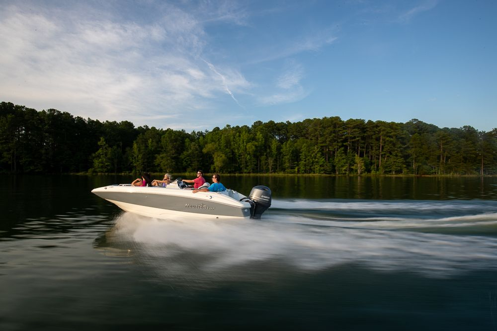 Couples cruising a lake in a NauticStar 193SC Deck Boat