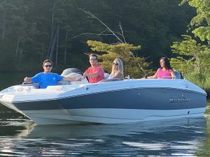 Two couples relax in a 293 Single Console Deck Boat on the calm waters of a Tenessee River Valley lake.