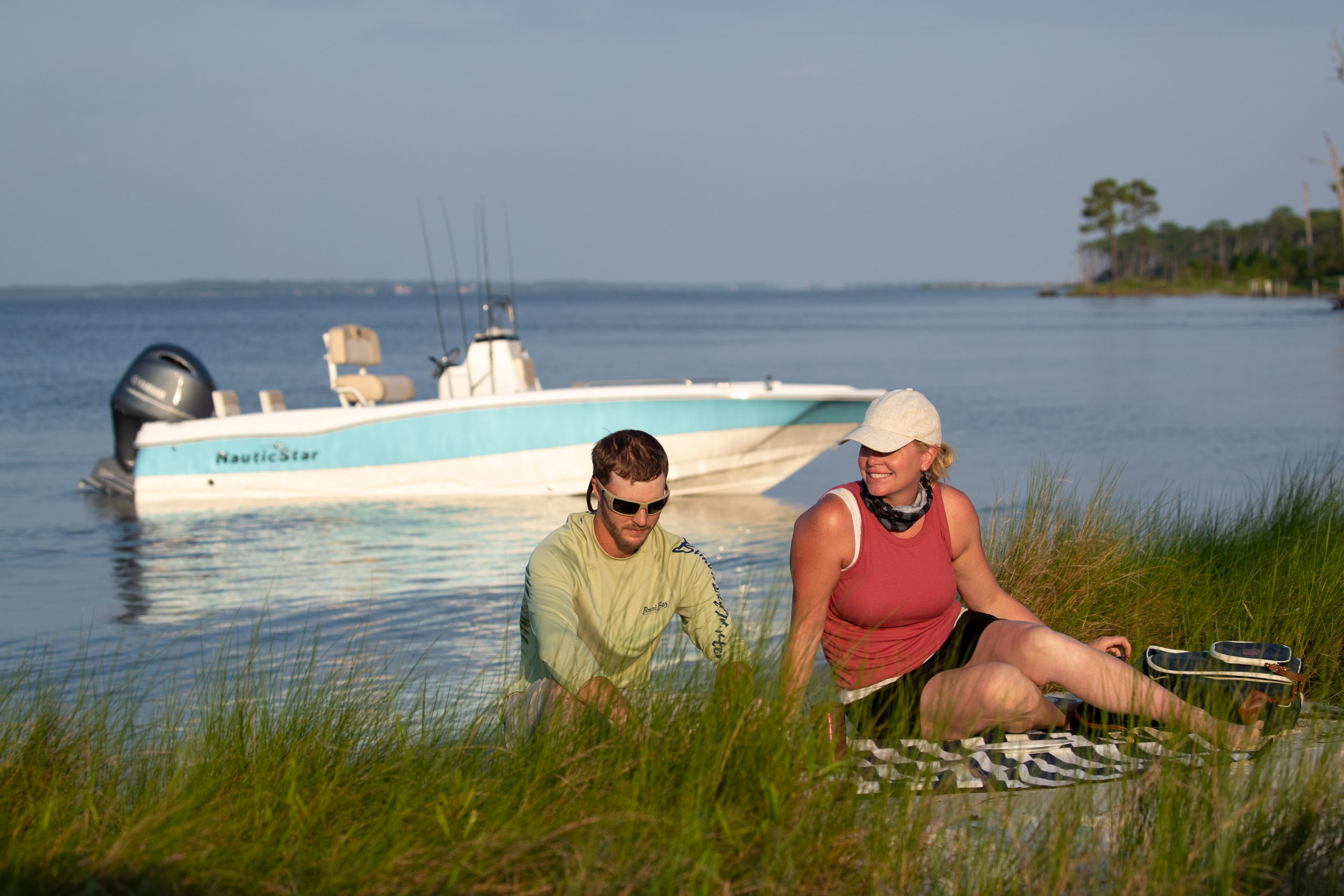 Couple picnicking on the beach in front of NauticStar 211 Hybrid bay boat