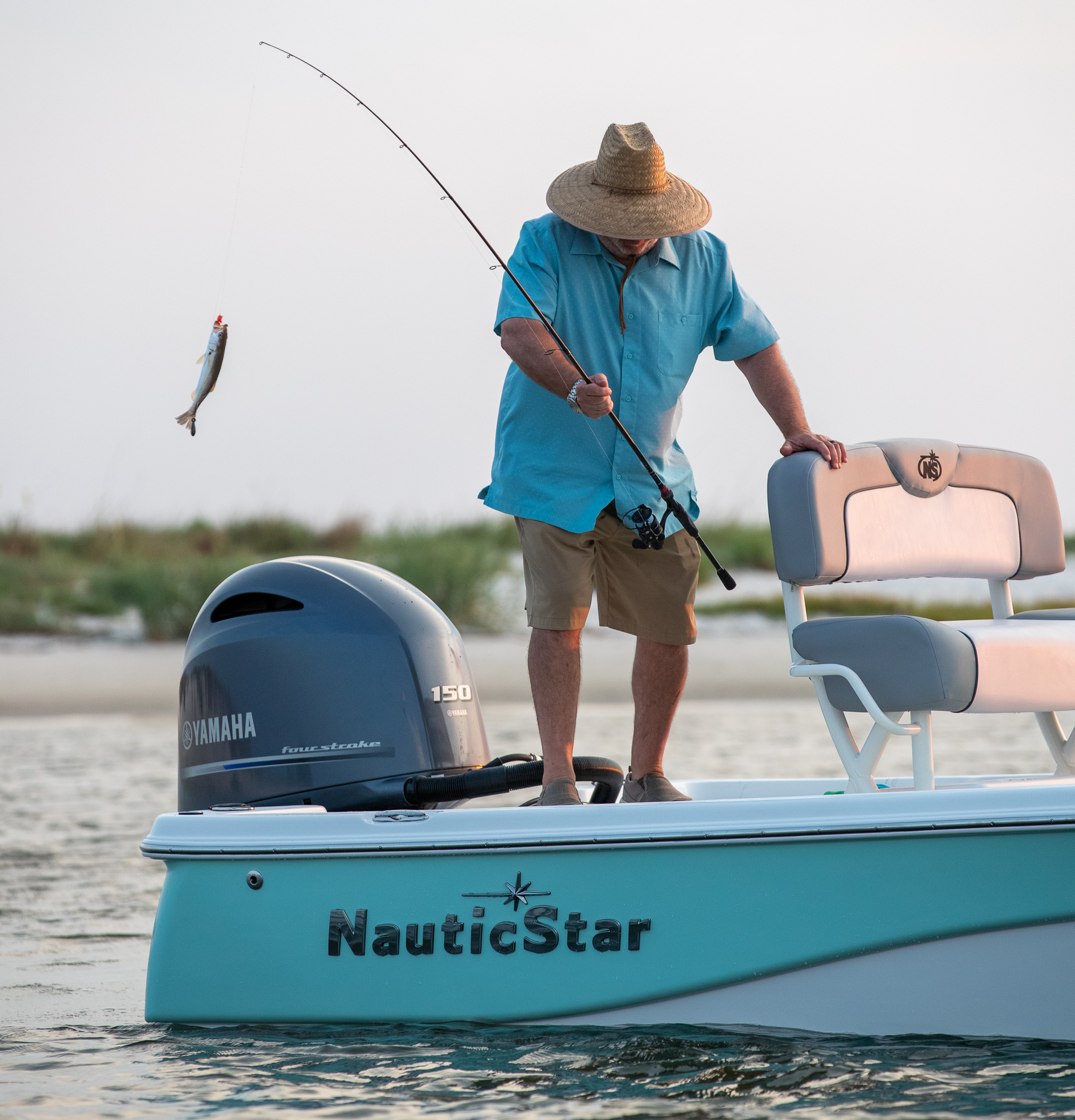 A man catches a fish off the aft deck of a NauticStar 215 Bay boat