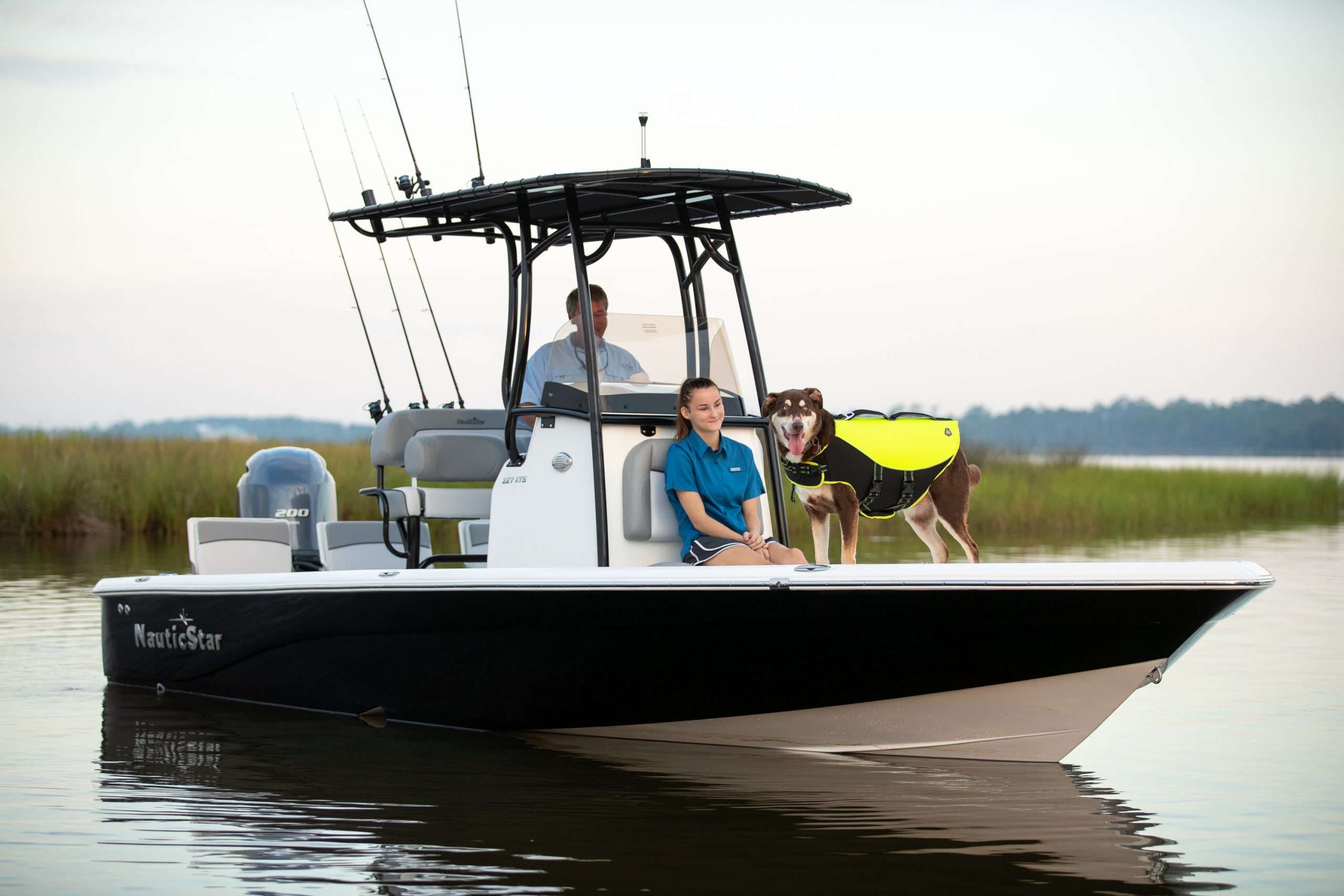 A family and dog sit at the helm and in the deck of a NauticStar 227XTS boat