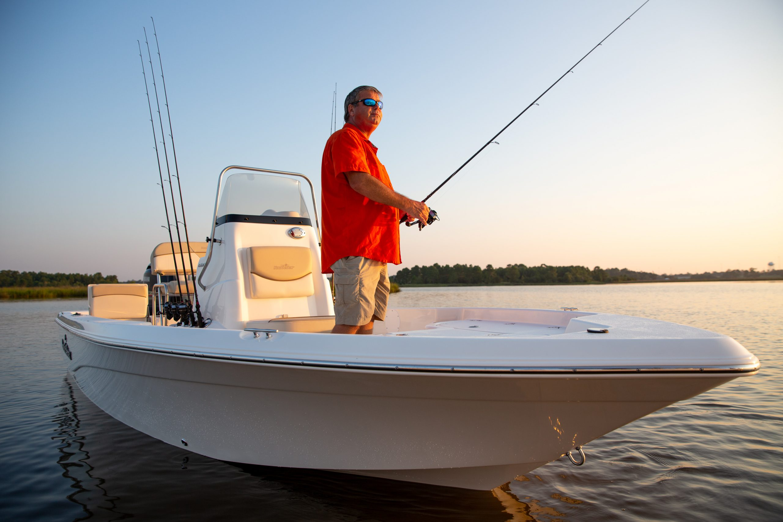 A man fishes near the center console seat of a NauticStar 195XTS boat at dawn