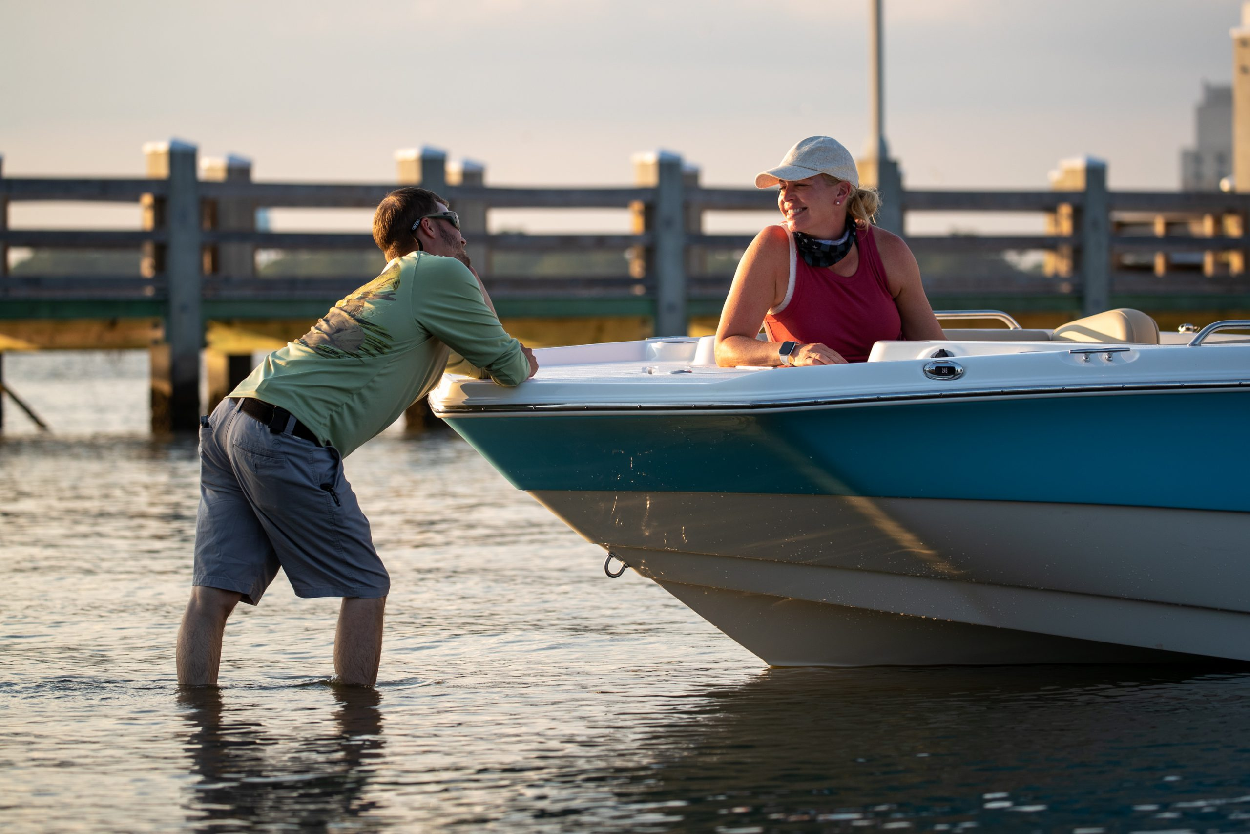 A man and woman talk at the bow of a NauticStar 211 Hybrid, while he pushes it away from the beach