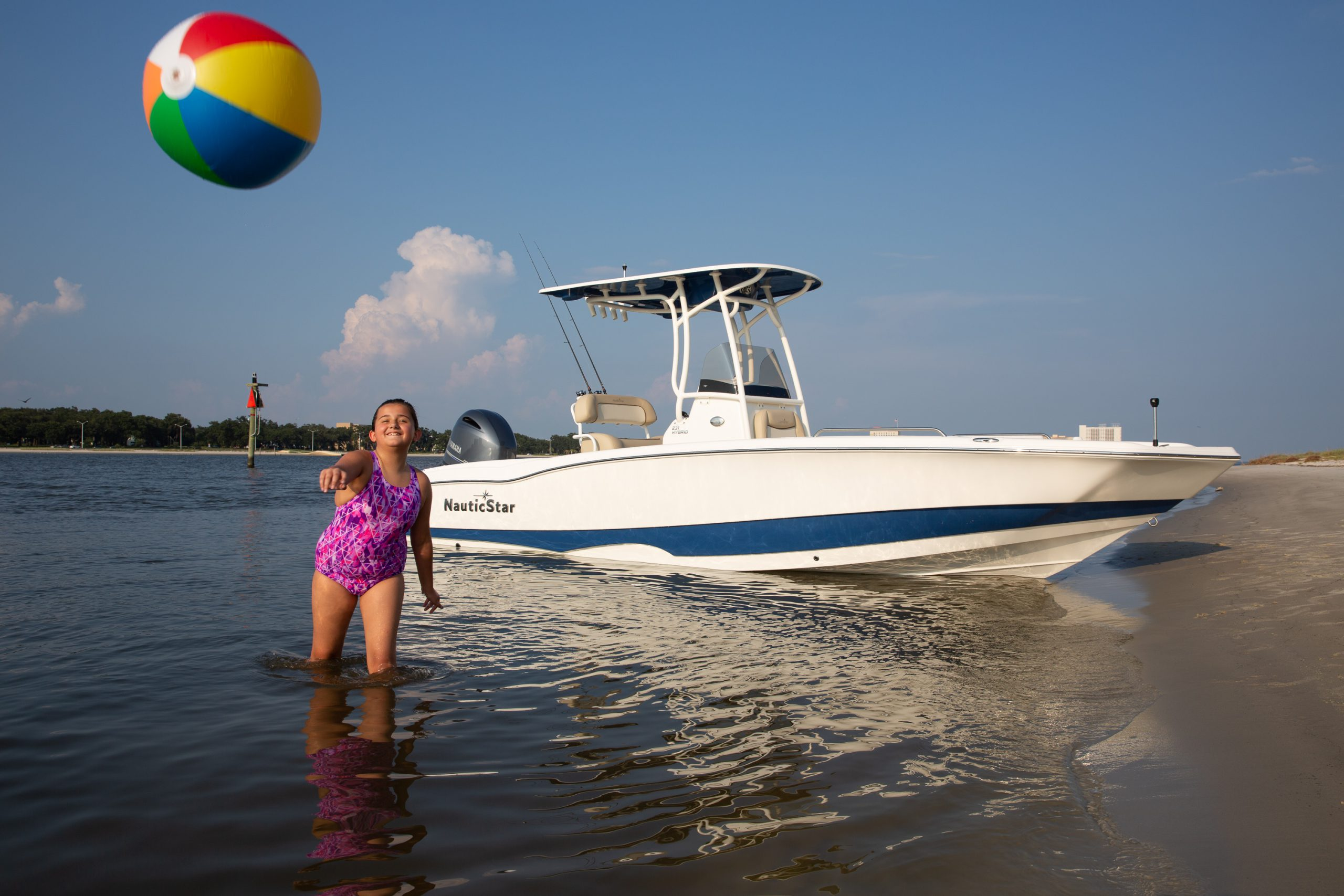 Girl tosses beachball at camera with a NauticStar 231 Hybrid boat beached behind her