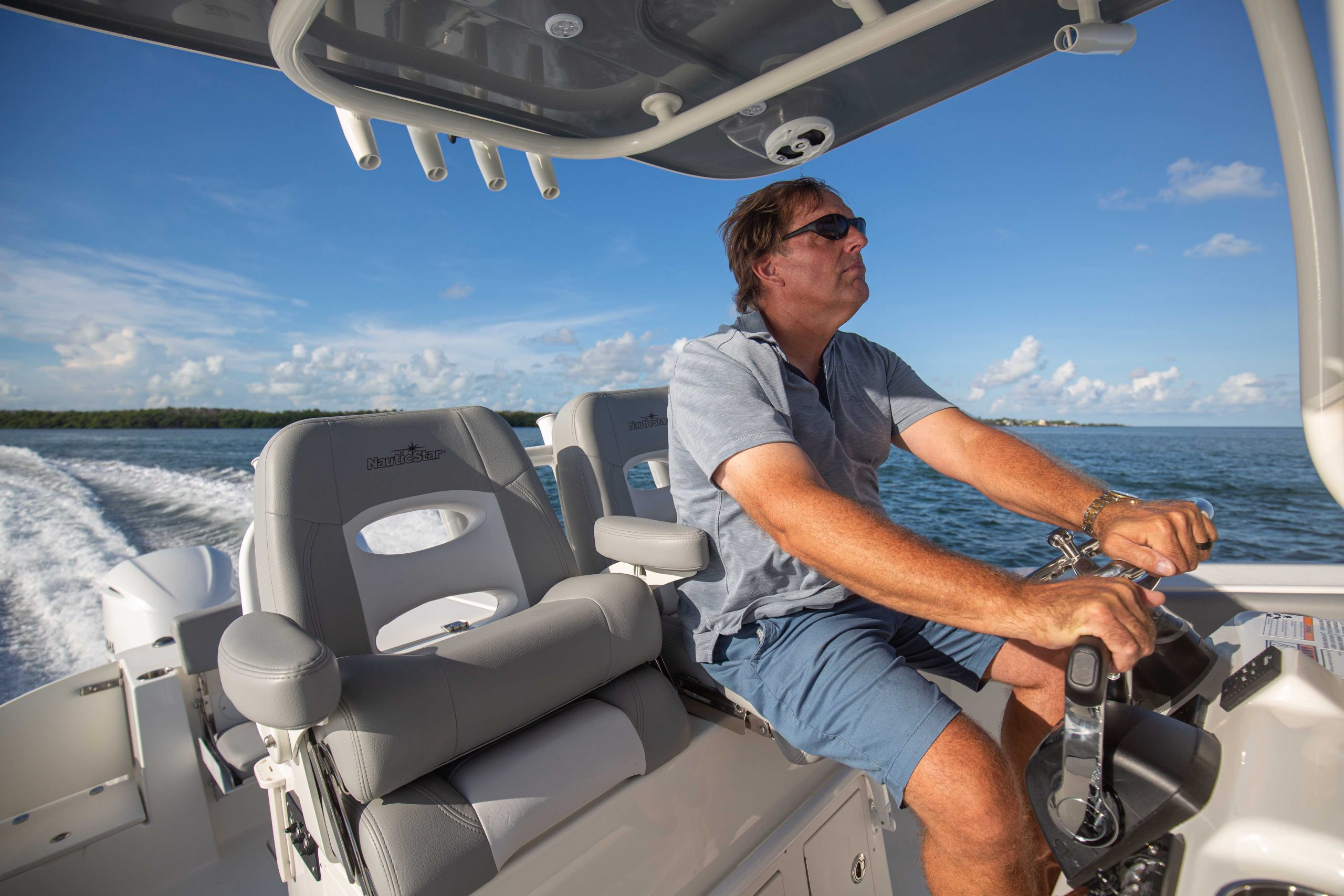 A captain drives at the helm of a NauticStar 28XS center console boat under a powder coated T Top