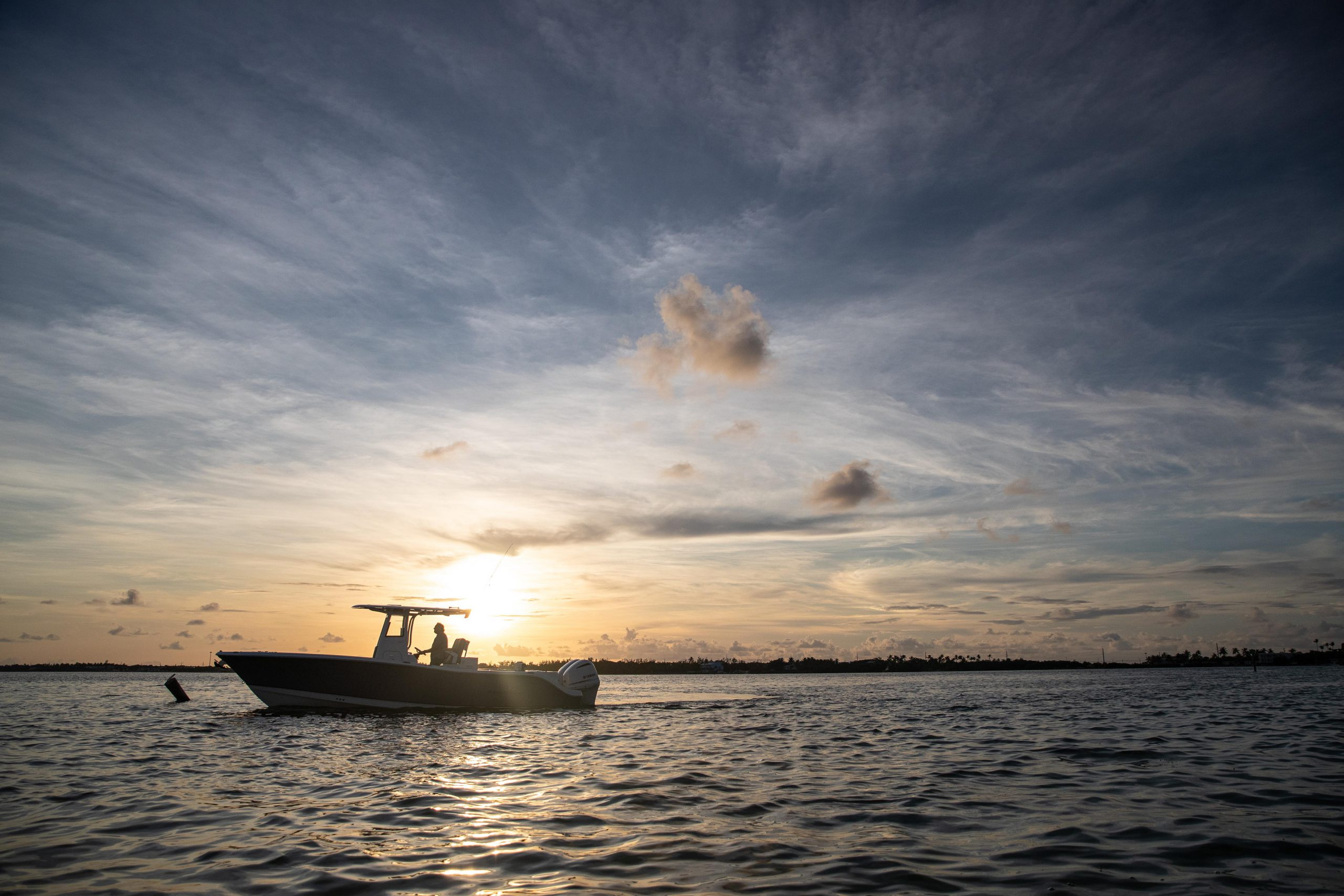A NauticStar 28XS boat glides across the sunset-lit ocean with clouds stretching above