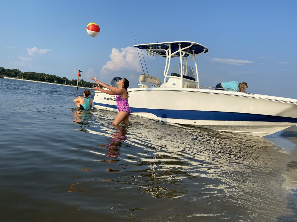 Girl Throws beach ball with friend in water next to a NauticStar 231 Hybrid